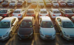 Image of a sunny car park full of post production cars